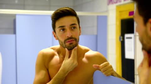 ung man att ta hand om hans ansikte i gymmet omklädningsrum - kroppsvård bildbanksvideor och videomaterial från bakom kulisserna