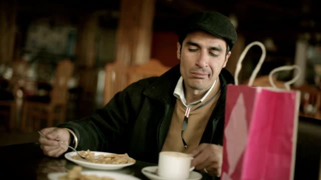 junger mann unter kaffeepause im restaurant nach dem einkauf - schiebermütze stock-videos und b-roll-filmmaterial