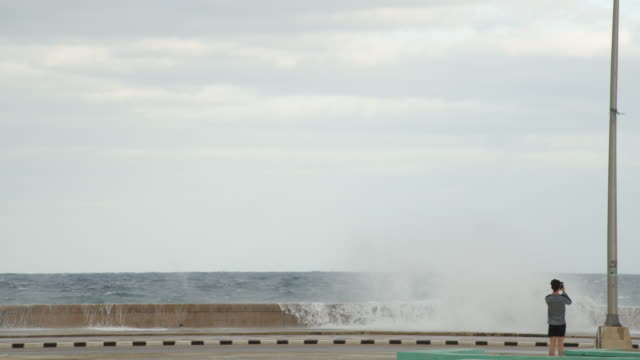 vídeos y material grabado en eventos de stock de young man taking mobile phone pictures of the sea waves surging onto the malecon coastal road in havana, cuba - pared de cemento