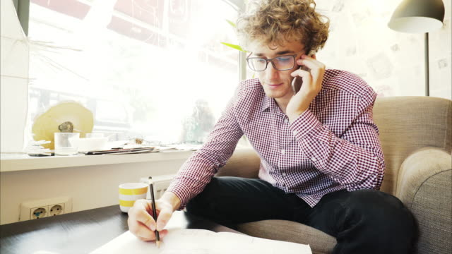 Young man taking notes while talking at mobile phone.