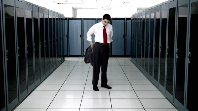 ws ds cu young man taking off vest and loosing tie in server room - see other clips from this shoot 1480 stock videos and b-roll footage