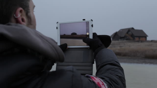 Young man taking photo of house with tablet in winter in rural Montana, USA.