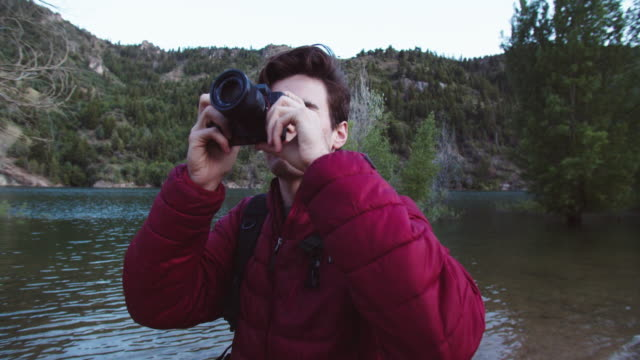 cu young man taking photos in the mountains - equipment点の映像素材/bロール