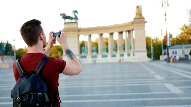 Young man taking photos of big city
