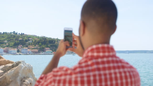 Young man taking photos of the beautiful coastal town on a sunny day