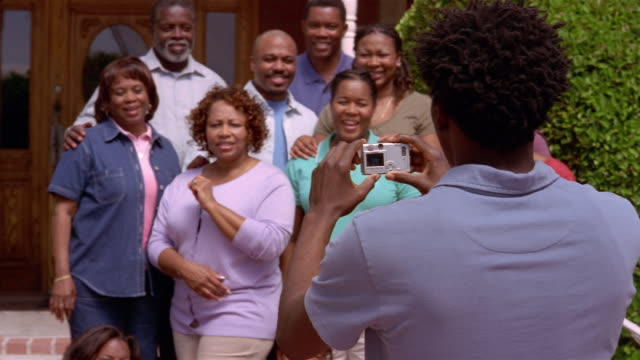 young man taking picture of family with digital camera at family reunion / mesa, arizona - organised group photo stock videos & royalty-free footage