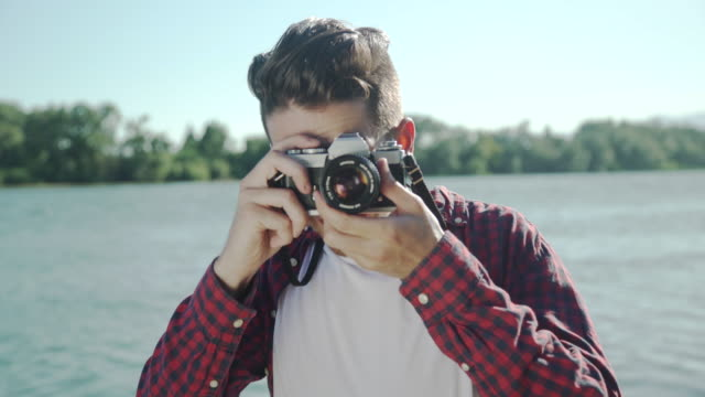 Young man taking pictures with an old-fashioned analog photography camera at sunset in the pier of a river. Casual hipster clothes and cool attitude.