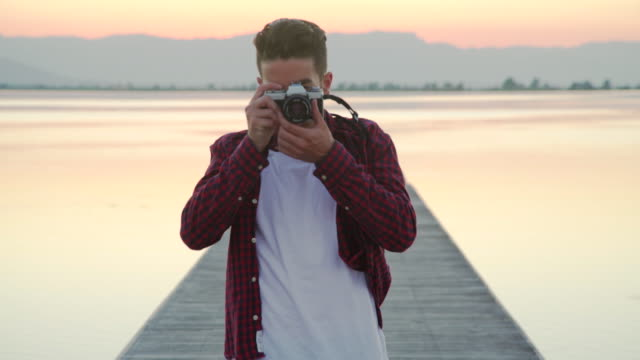 Young man taking pictures with an old-fashioned analog photography camera at sunset in the pier of a river.