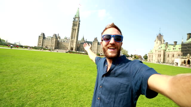 young man taking selfie at parliament hill ottawa - ottawa stock videos & royalty-free footage