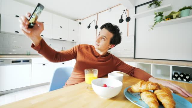 Junger Mann unter Selfies in der Küche.