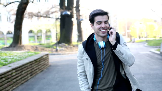 Young man talking by the phone in the city park