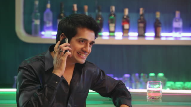 Young man talking in a mobile phone at bar counter