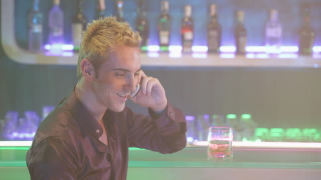 Young man talking on a mobile phone at bar counter