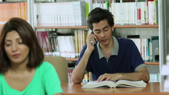 Young man talking on a mobile phone in the library, Noida, Uttar Pradesh, India