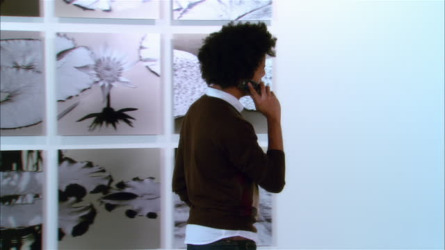 young man talking on cell phone while looking at contemporary artwork in gallery - art museum stock videos & royalty-free footage