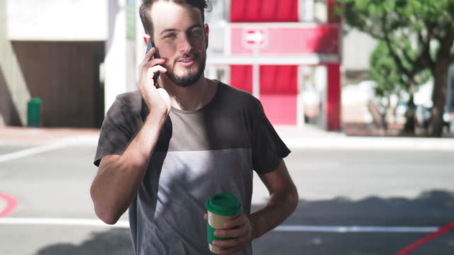 young man talking on his phone while walking - t shirt stock videos and b-roll footage