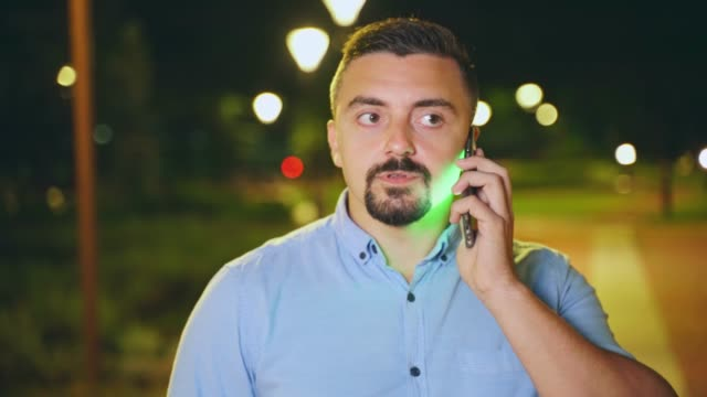 Young man talking on his smart phone outdoors at night close up