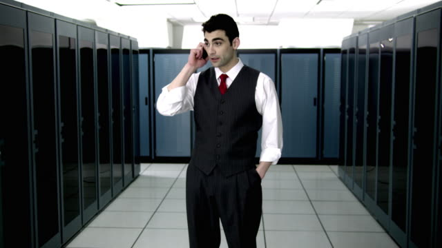 ws ds cu young man talking on mobile phone in server room - see other clips from this shoot 1480 stock videos and b-roll footage