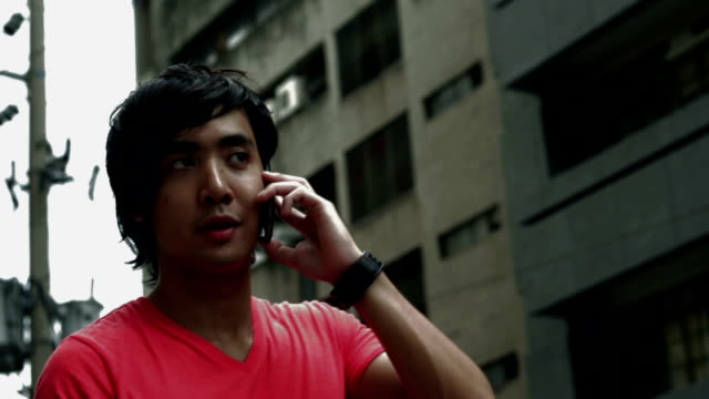 young man talking on phone by the street - philippines stock videos & royalty-free footage