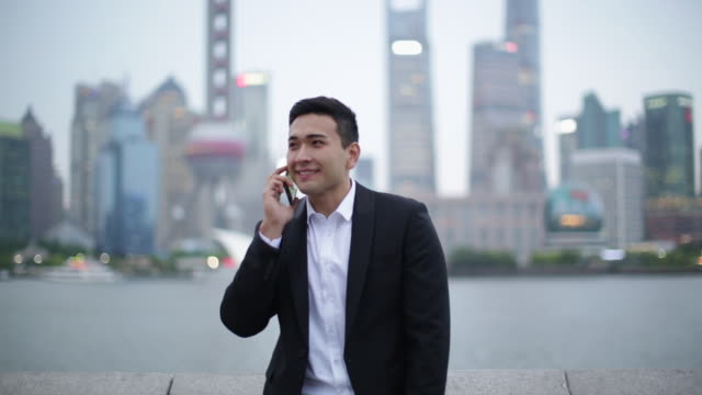 WS young man talking on phone in front of Shanghai skyline, evening