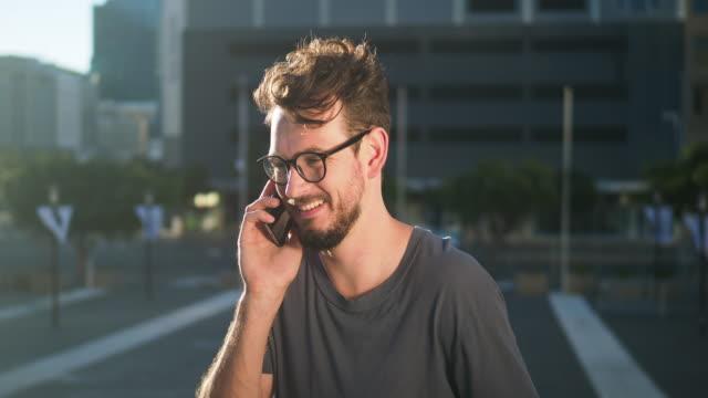 young man talking on phone - engångsmugg bildbanksvideor och videomaterial från bakom kulisserna