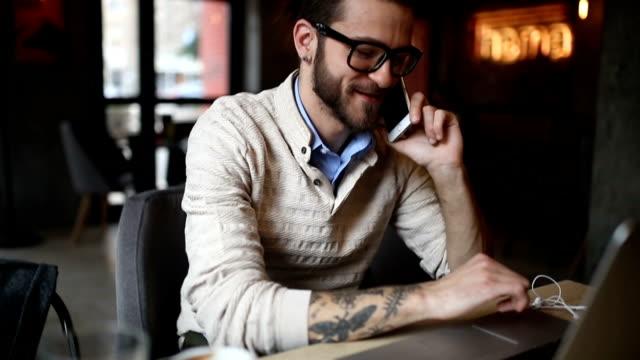 Junger Mann am Telefon und Computer im café