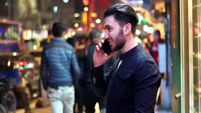 Young man talking on the phone outdoors at night time