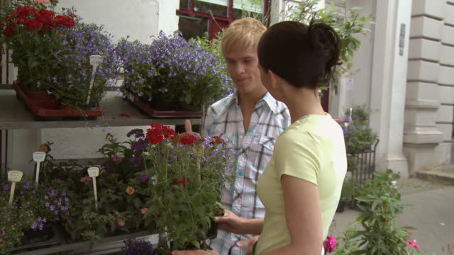 cu zo ms young man talking to woman and selecting flowers in front of flower shop / berlin, germany - flower shop stock videos and b-roll footage