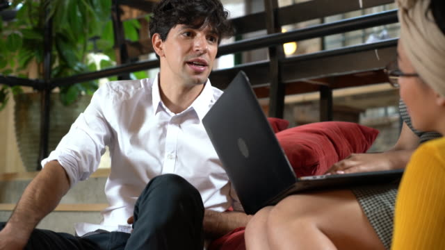 young man talking to women with laptop - cushion stock videos & royalty-free footage