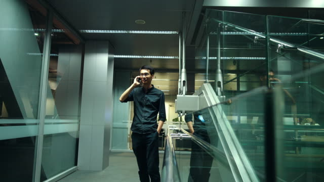 Young man talking with smart phone in a modern office
