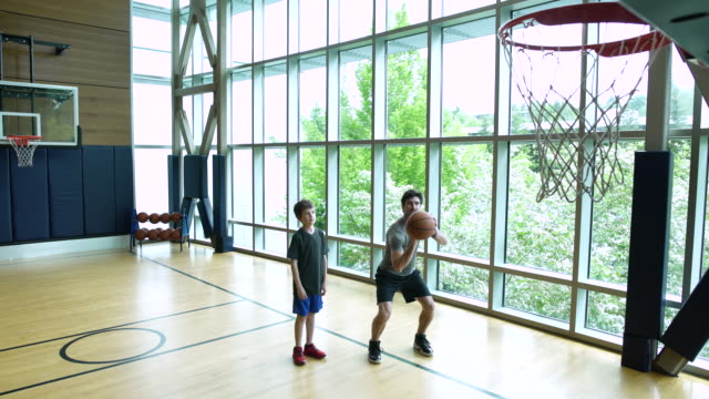 Young man teaching boy how to play basketball