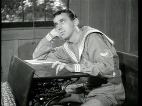 vidéos et rushes de 1945 montage a young man teasing a girl in class - tirer la langue