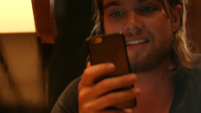 a young man texting and searching his cell phone indoors in new york city - long hair stock videos & royalty-free footage