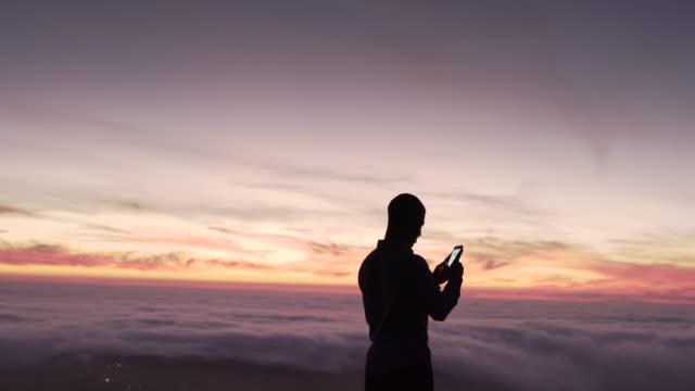 vidéos et rushes de ms young man texting at dusk - communication