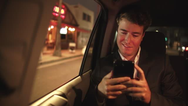 vídeos de stock e filmes b-roll de cu young man texting in a taxi at night - fato
