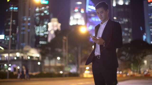 MS Young man texting in the city at night