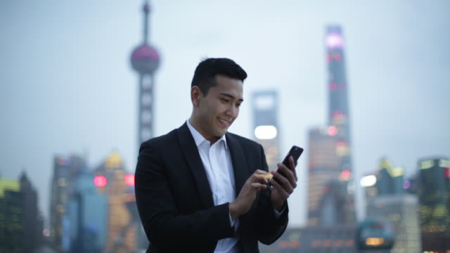 young man texting on a phone in shanghai in the evening. - テレビ塔点の映像素材/bロール