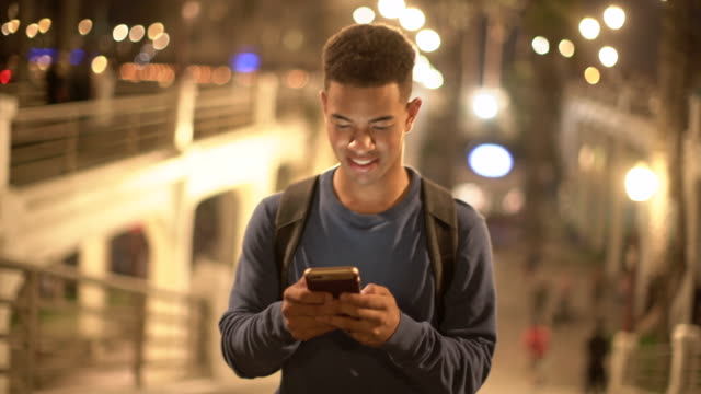 ms young man texting on his phone at night. - mixed race person stock videos & royalty-free footage