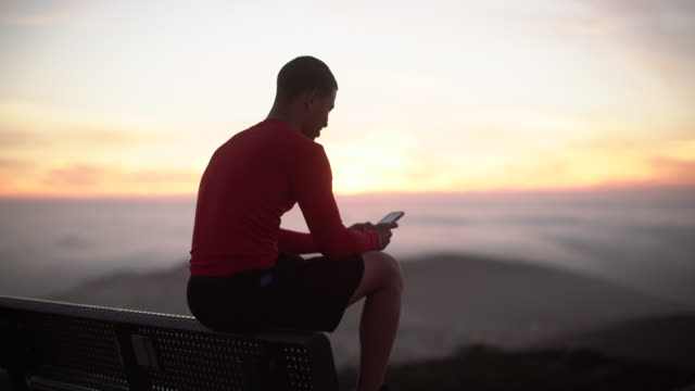 ms young man texting on his phone at sunset - hill stock videos & royalty-free footage
