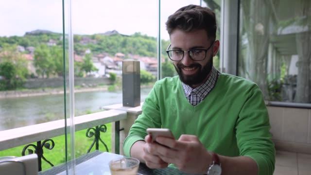 vídeos y material grabado en eventos de stock de joven enviando mensajes de texto en su teléfono en el café de la calle - mesa baja de salón