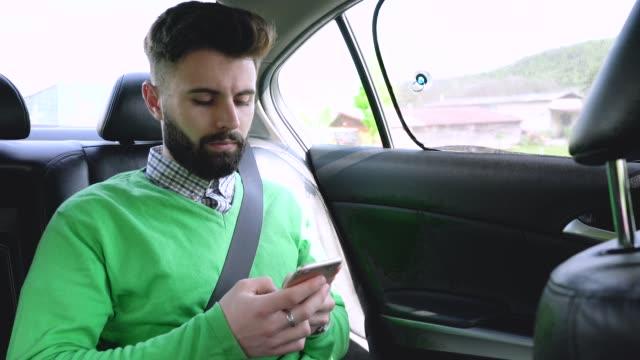 vídeos y material grabado en eventos de stock de joven enviando mensajes de texto en su teléfono en el coche - pasajero