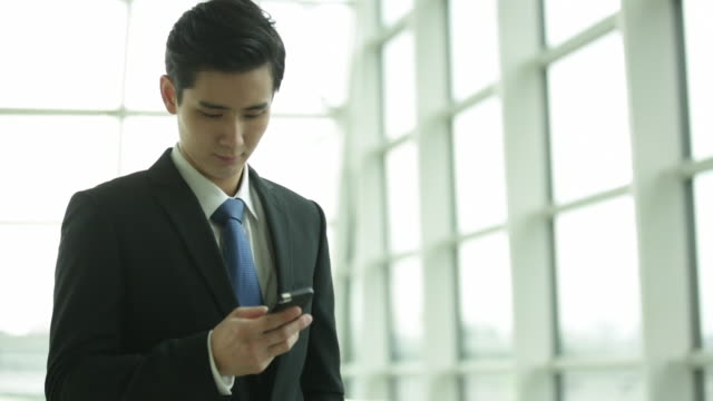 vidéos et rushes de ms young man texting on phone inside an office. - regarder vers le bas