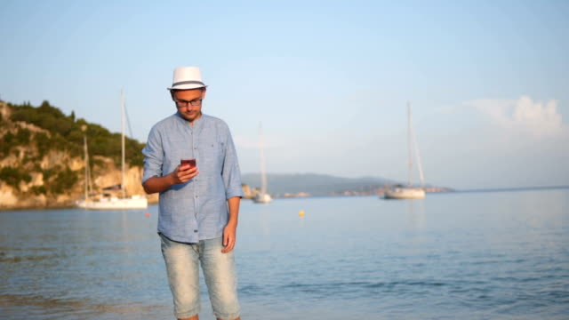 young man texting on the beach - contented emotion stock videos & royalty-free footage