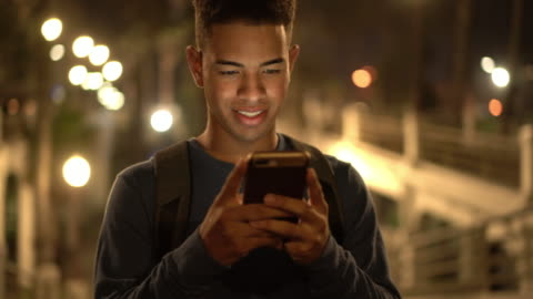 vídeos y material grabado en eventos de stock de cu ts young man texting on the street at night - cabello negro