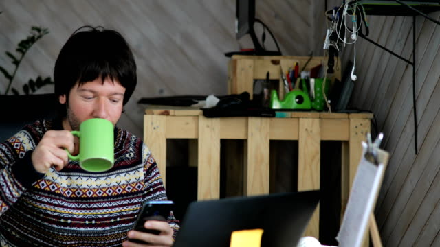 young man texting while drinking coffee in home office - infectious disease stock videos & royalty-free footage