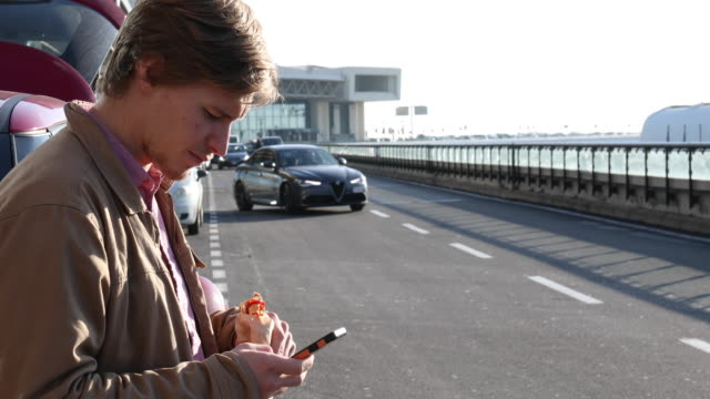 Young man texts while eating sandwich beside car