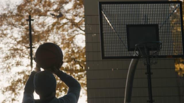 junger mann werfen basketball in richtung hoop - basketball stock-videos und b-roll-filmmaterial