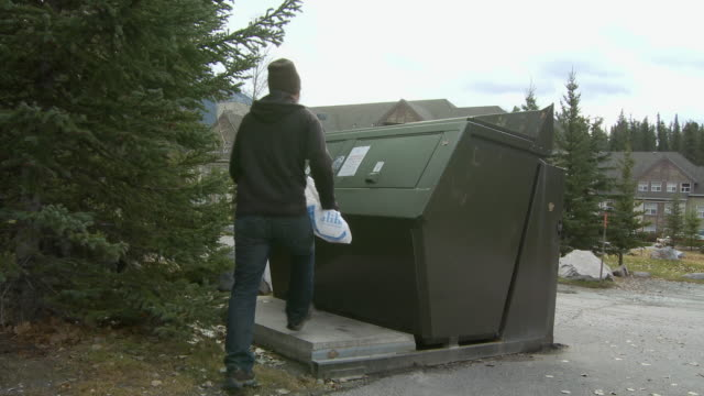 WS Young man throwing garbage into bear proof garbage bin / Banff, Alberta, Canada
