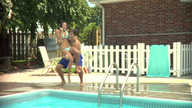 ms, young man throwing teenage girl (16-17) into swimming pool, middlesex, new jersey, usa - mischief stock videos & royalty-free footage