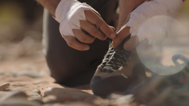 CU. Young man tightens and double laces climbing shoes before rock climbing expedition.